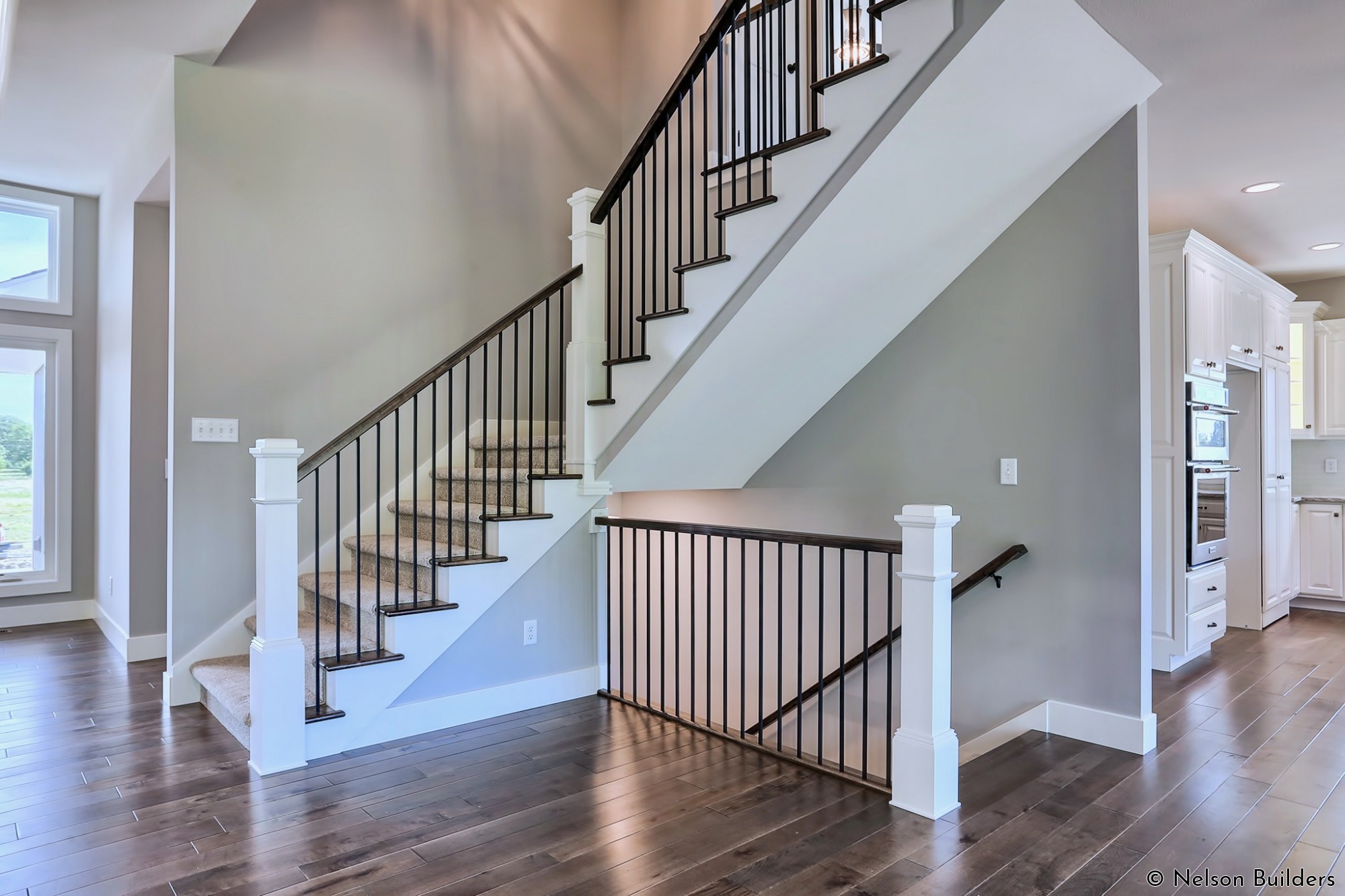 The stacked stairways are a simple statement with the black iron balusters and exposed wood treads.