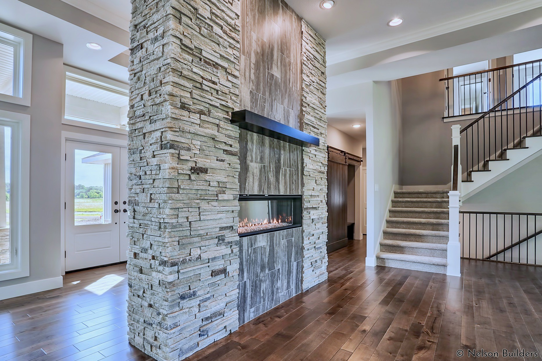 The linear fireplace is given a contemporary look with a mix of gray stone and ceramic tile oriented vertically.