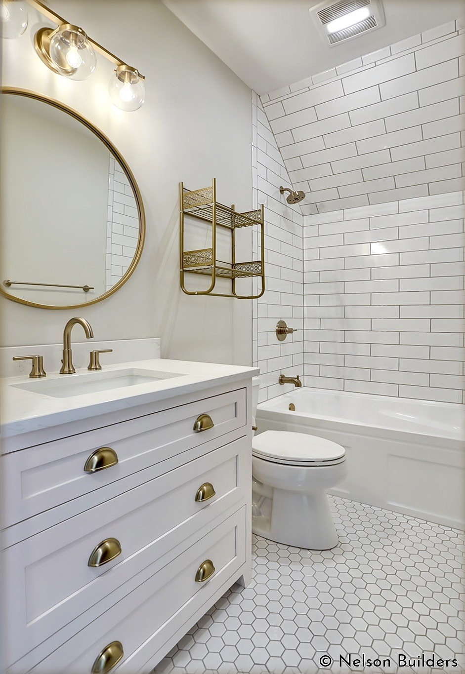 One bedroom features a private bathroom that is decorated with white subway tile, a light rose colored vanity, and brushed brass accents.