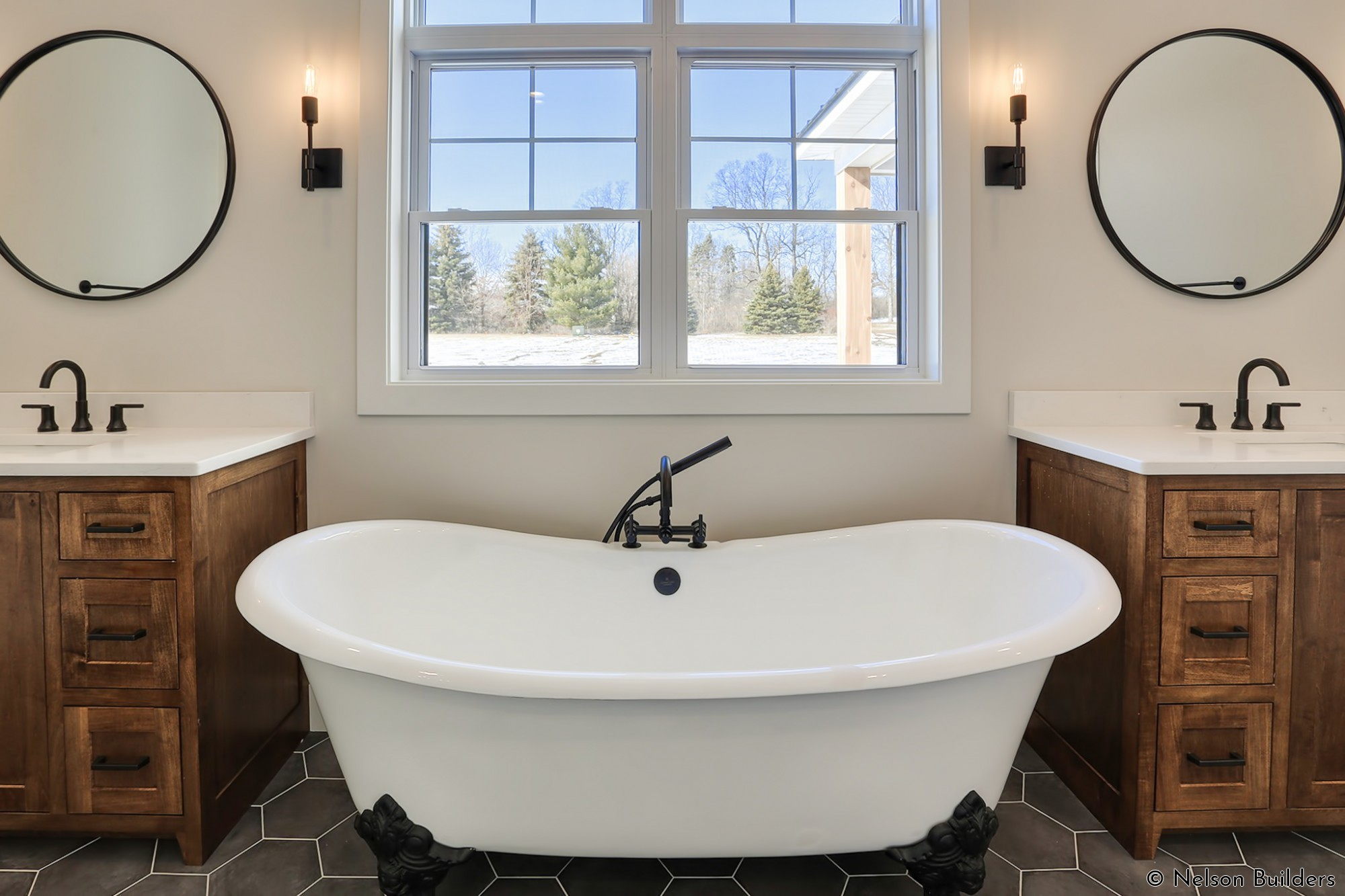 The modern clawfoot tub with black feet is the main accent of the master bath, complete with plenty of natural light.
