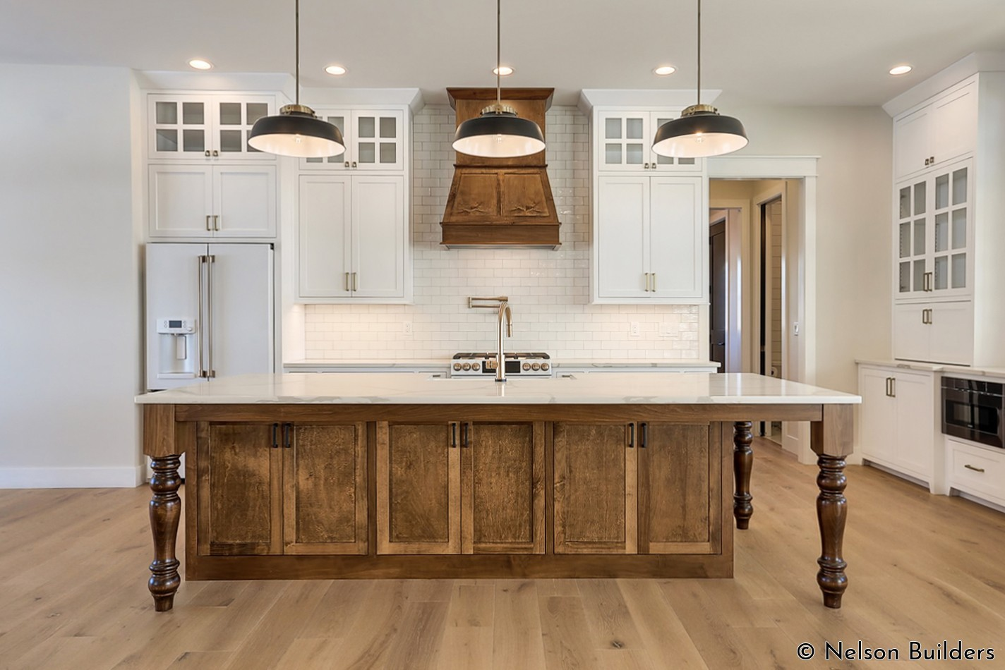 The 10-foot ceilings in this farmhouse kitchen are balanced out with full height cabinetry and 8-foot doors.