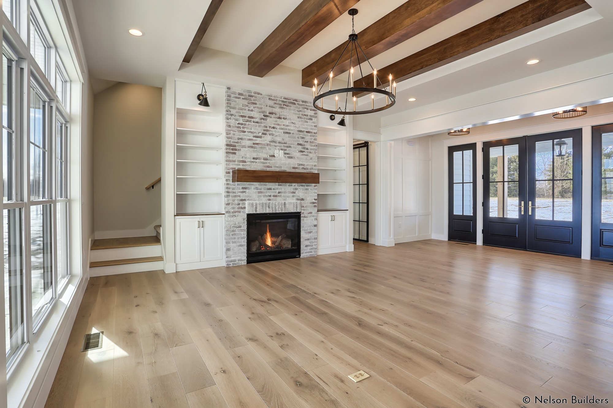 The fireplace is flanked on both sides with built-in bookcases, including library lights for accent lighting.