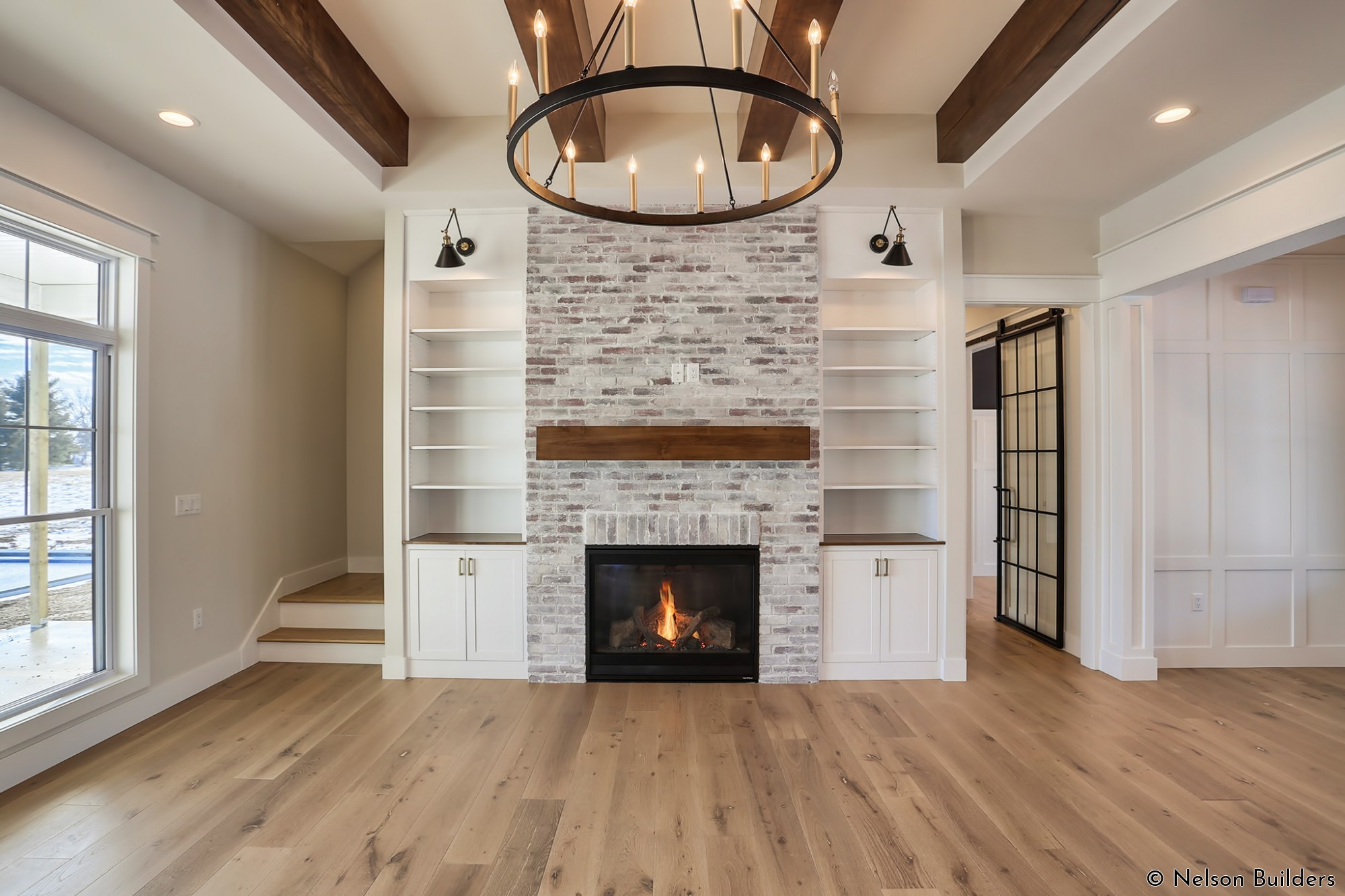 The great room of this custom home is flanked with glass on both sides, a brick fireplace focal point, and wood beams in the ceiling.