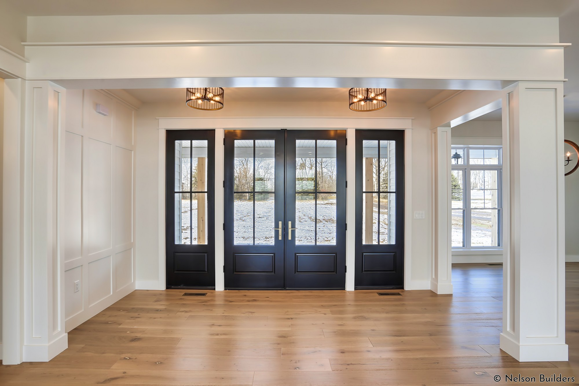 The 8-foot tall front doors are balanced inside a formal foyer, complete with paneled columns and wall details.