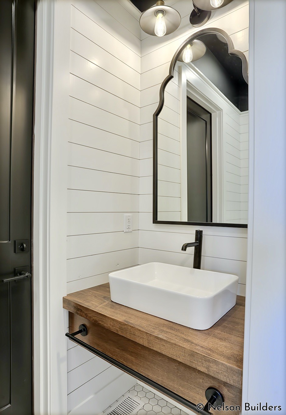 The powder room doubles as a pool bathroom for outside access and is lined with shiplap nearly to the ceiling.