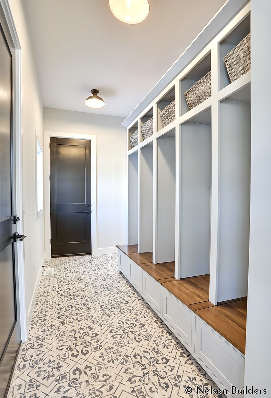 The owner's entry hall is lined with enough cubbies for every family member to have their own storage for everyday items. The bench top even folds up for more storage underneath.