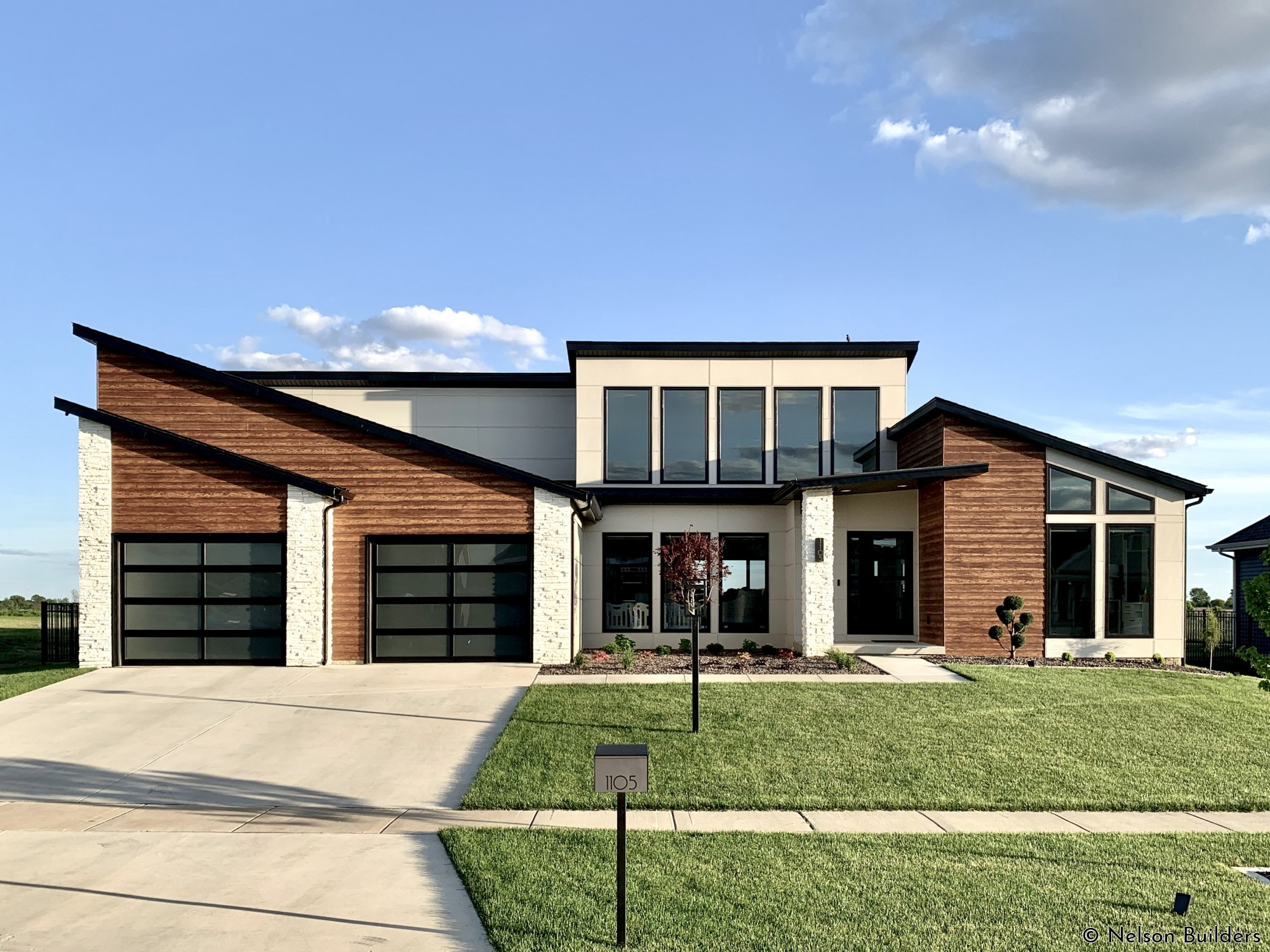 The exterior of this custom modern home is accented with several different types of fiber cement, from panels with shadow gaps to stained lap siding.
