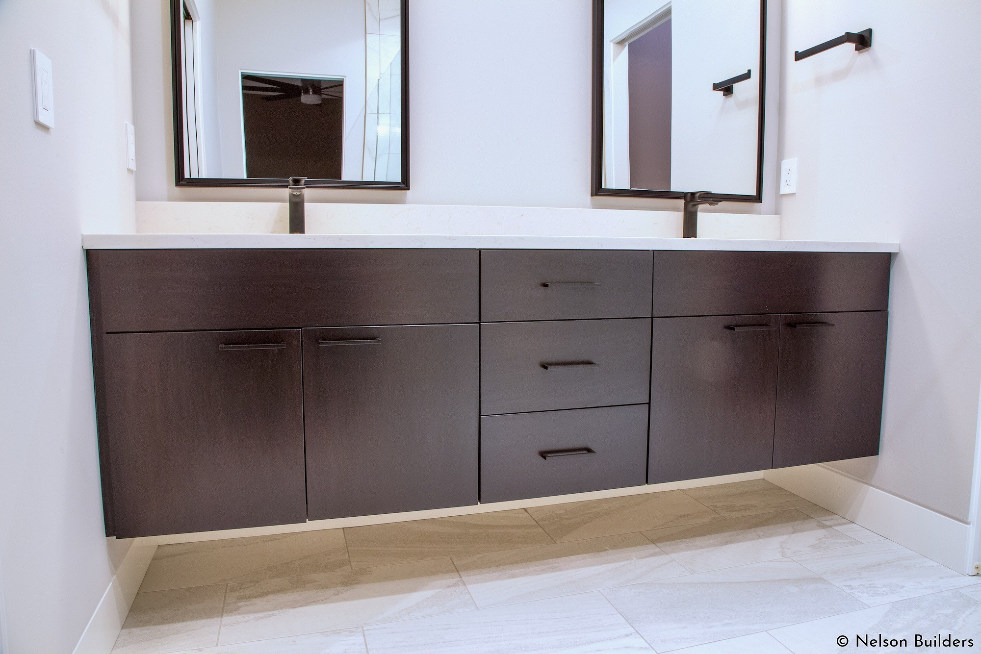 The bathrooms feature floating vanities that allow for open space below, highlighting the flush base detail.