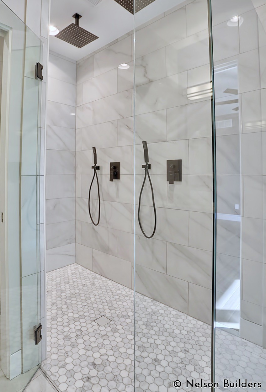 The master shower features two shower heads and a curbless design, for a clean, modern aesthetic.