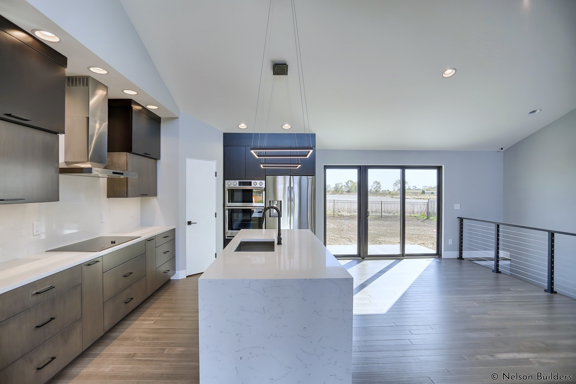 The eat-in kitchen is flanked on one side by a cable railing and the waterfall quartz island on the other.