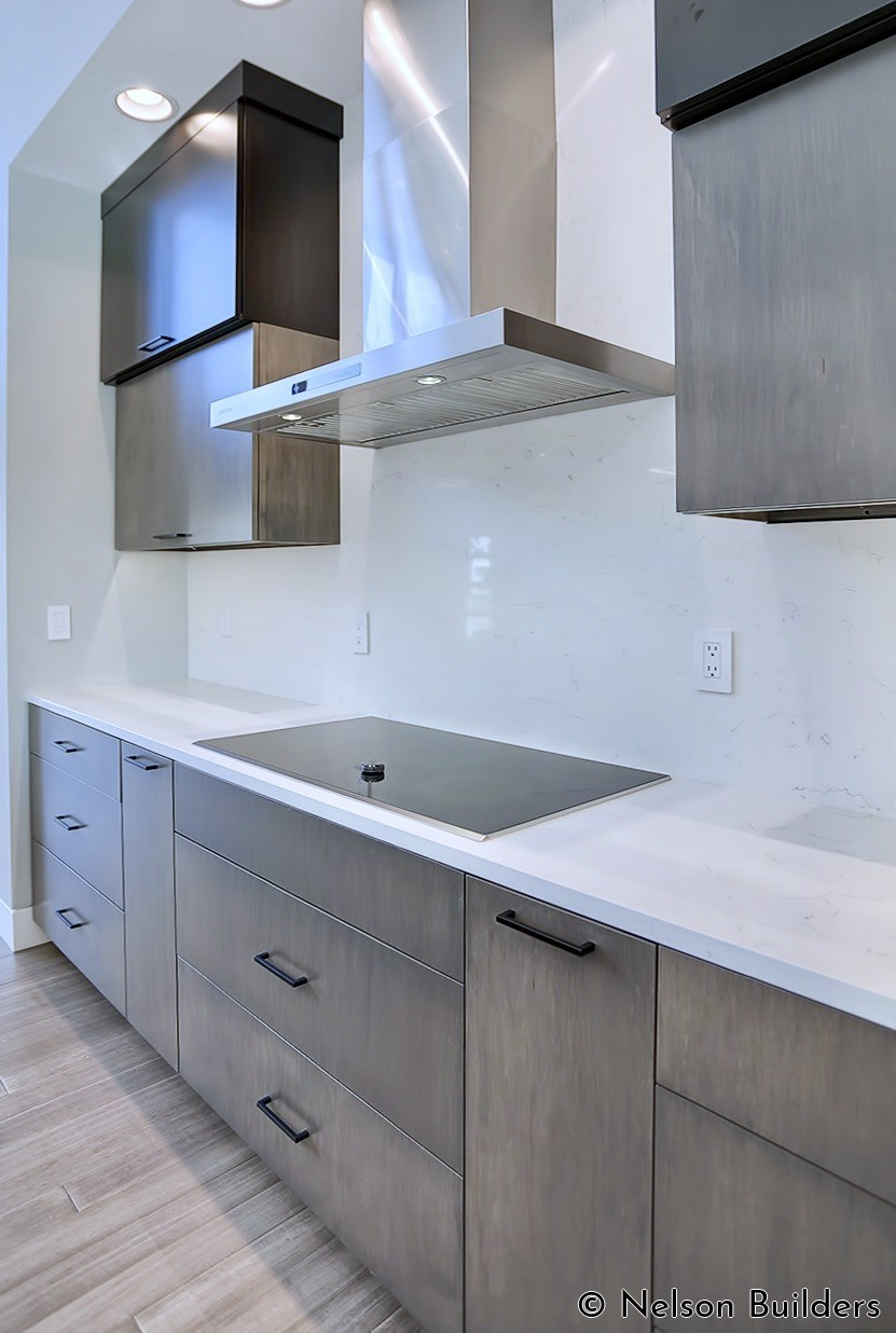 The kitchen was designed to be very minimal to keep with the modern design. The slab backsplash fills in the space between the vertically opening upper cabinets.