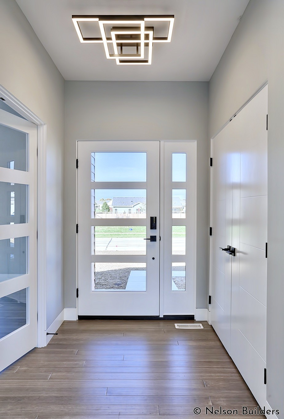 The entry foyer is accented with several glass doors and a modern LED bar fixture.