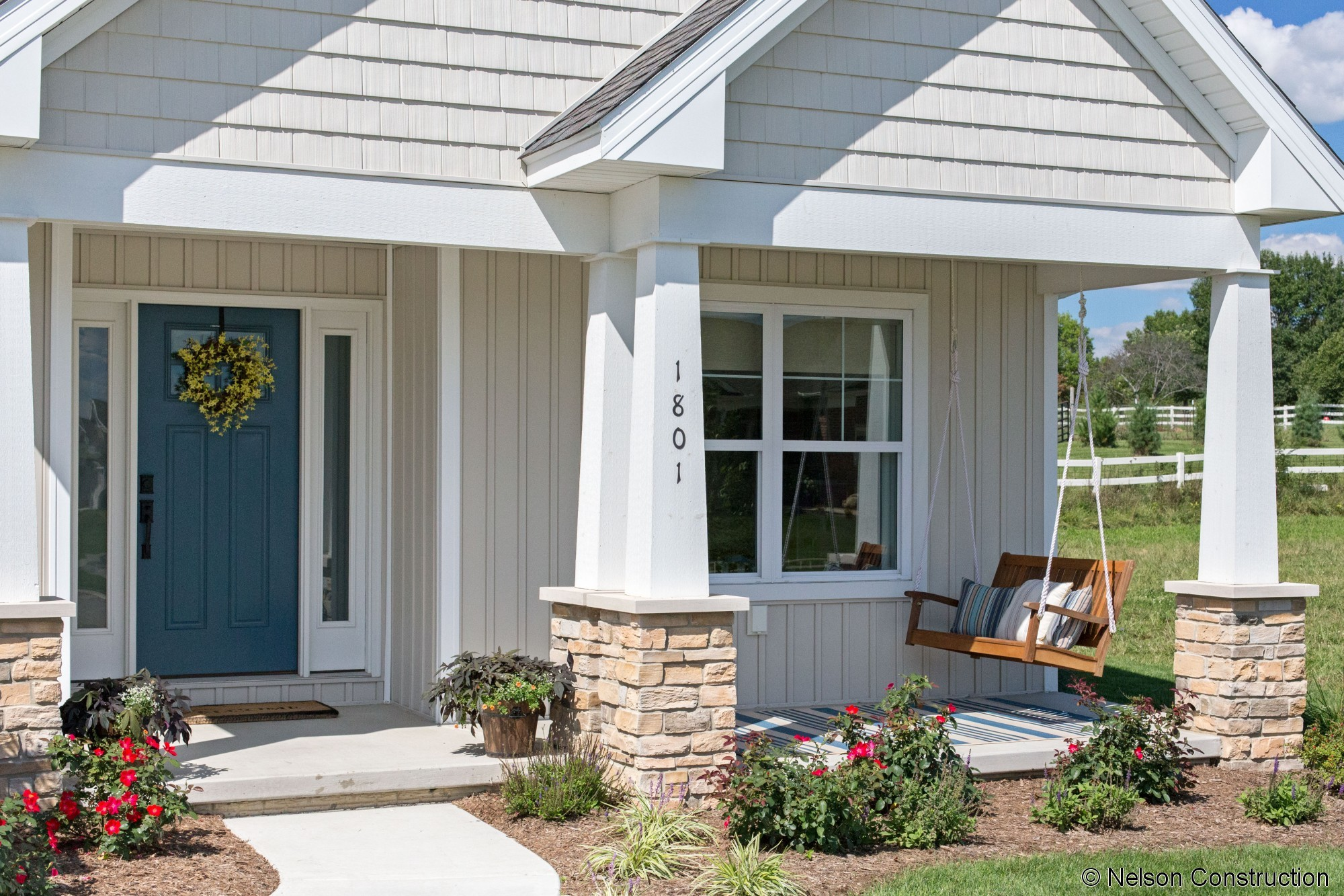 The front porch of this Sycamore home is warm and inviting with a porch swing to complete the space.