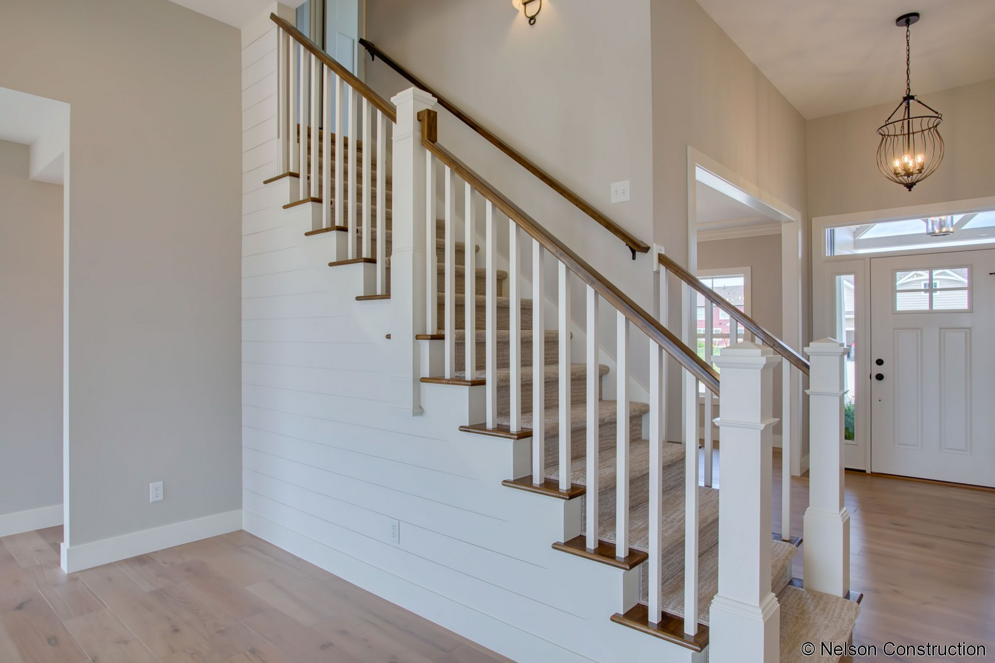The centerpiece of the living area in the new Cherrydale home is a shiplap clad staircase, serving as the focal point of the room.