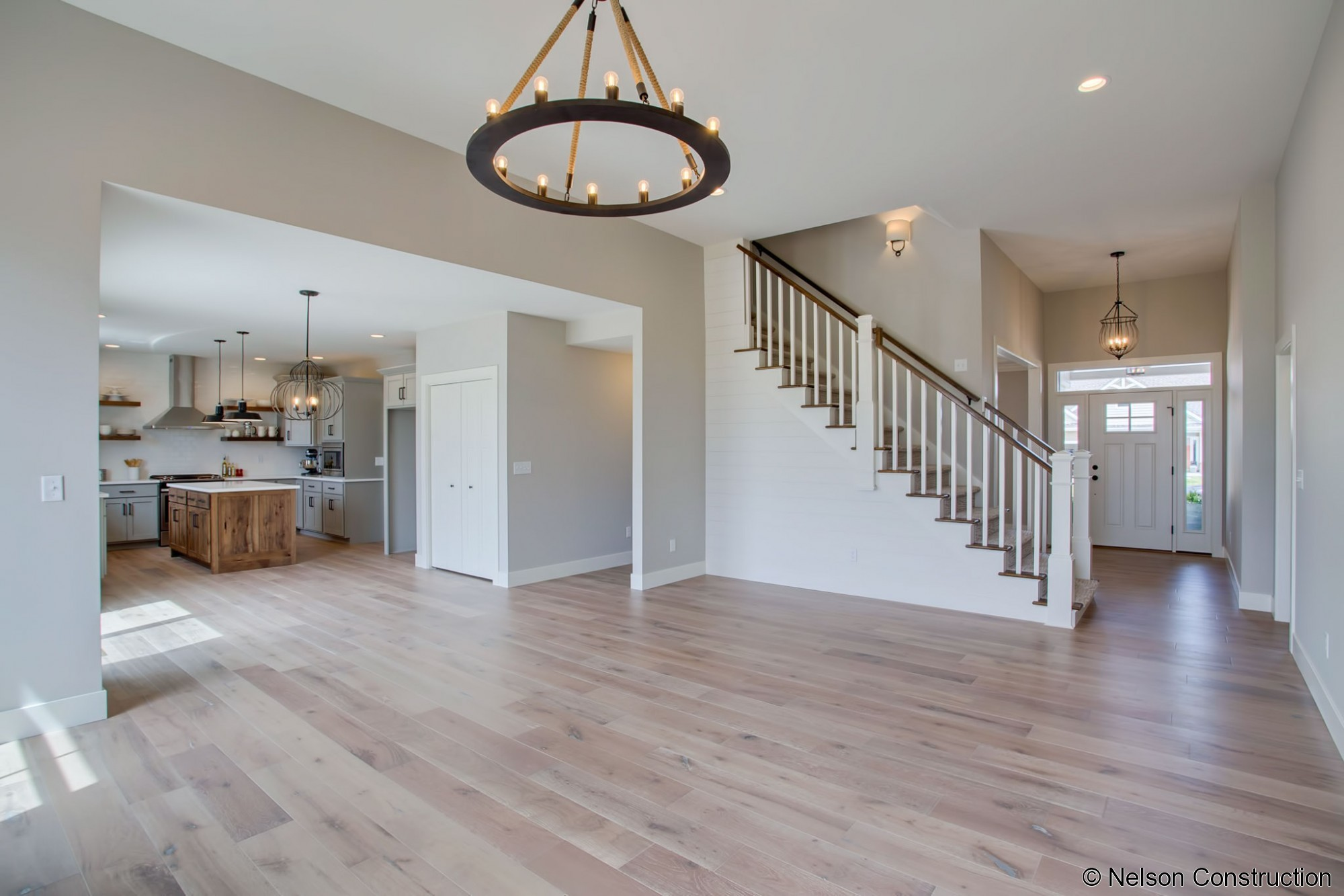 The family room, with its 11 foot ceilings and accent chandelier, opens to both the foyer and kitchen.