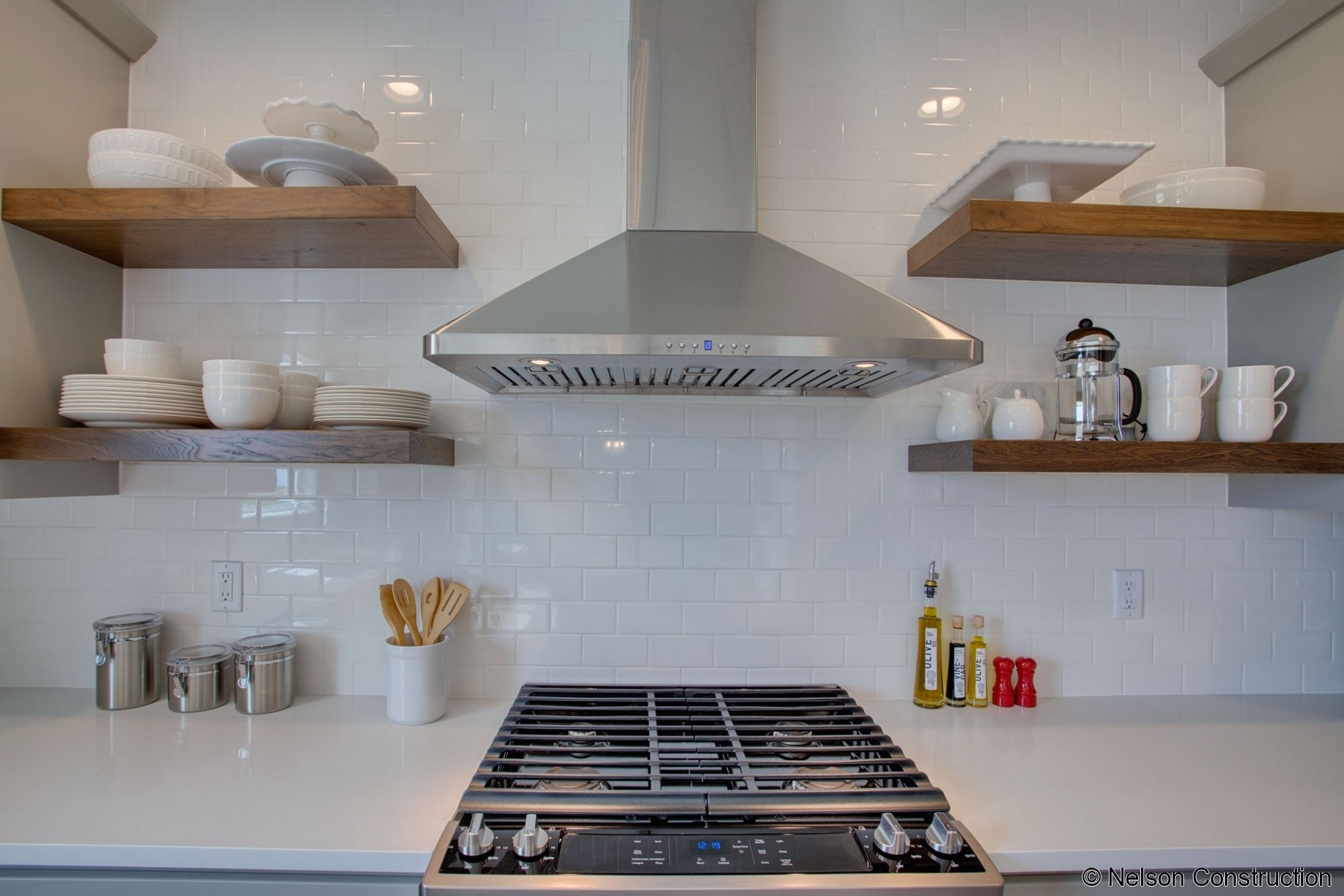 The designer inspired kitchen of this new home features floating shelves, subway tile backsplash, and a stainless hood.