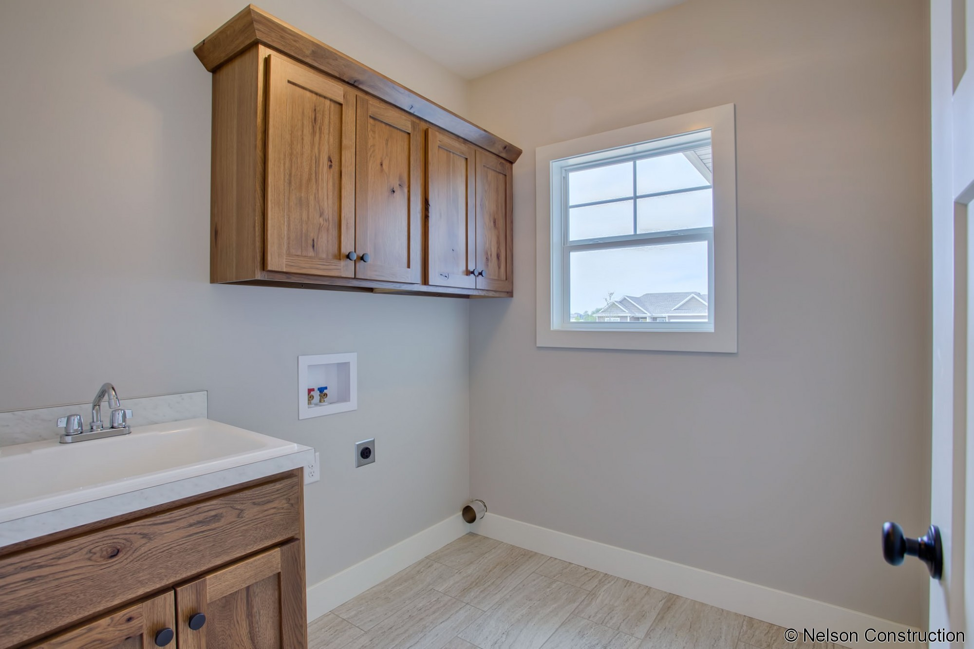 The laundry room in this Cherrydale has plenty of cabinets for storage and a large sink to make cleaning easier.