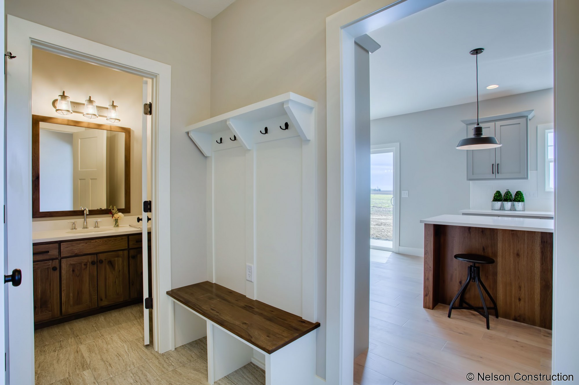 The drop zone between the garage and kitchen is open to the laundry, half bath, and kitchen.