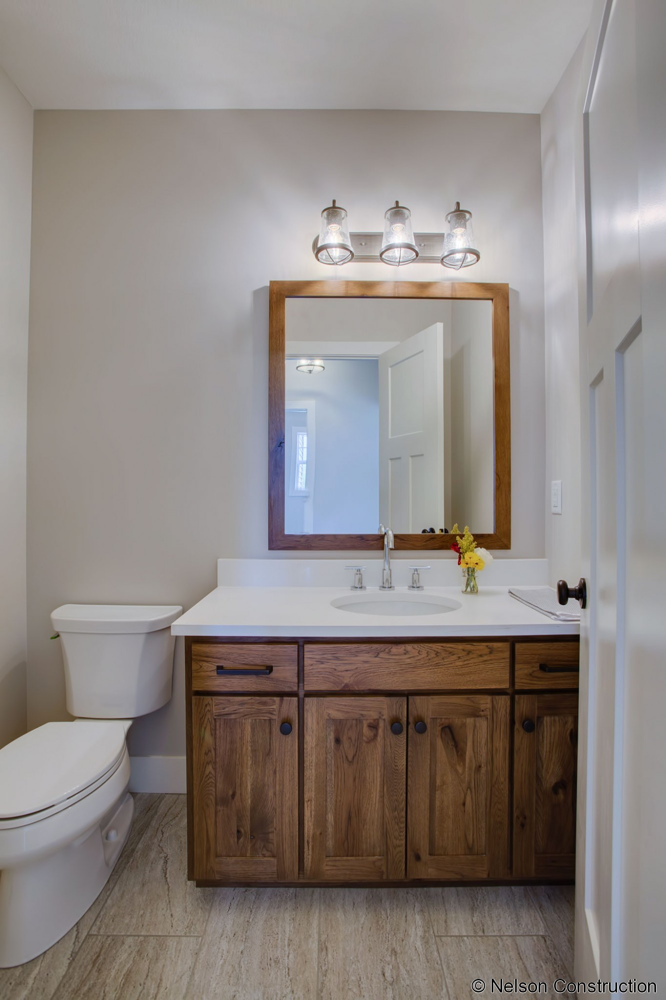 The half bath on the first floor is conveniently located off the kitchen and carries the designer inspired style found throughout the home.