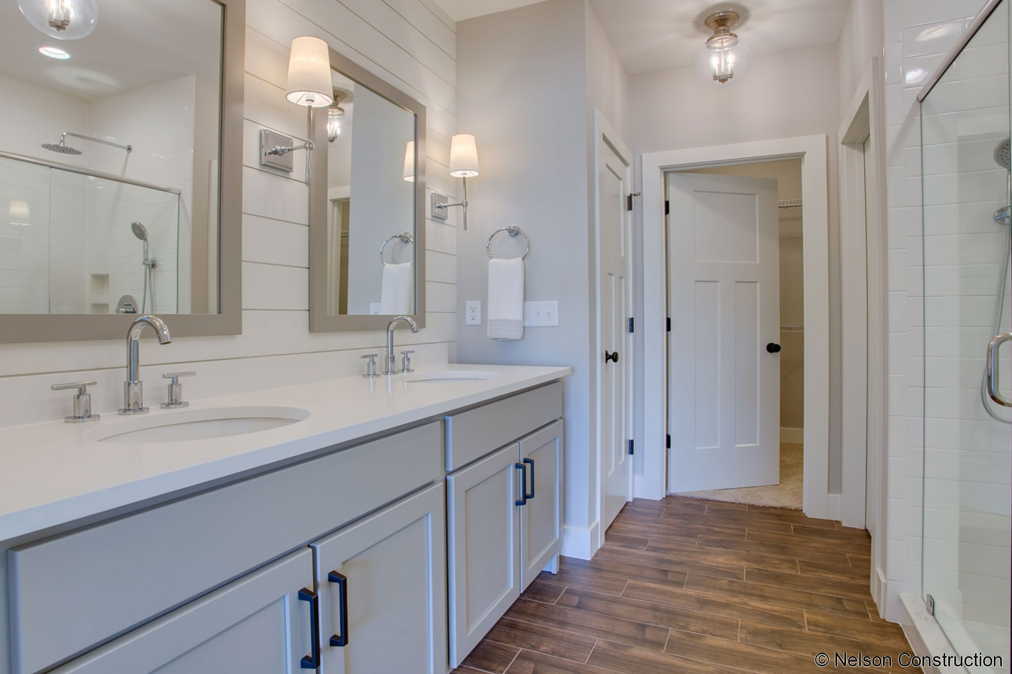 The beautiful master bath of this Cherrydale plan features shiplap accents and a huge walk in, subway-tile, shower.