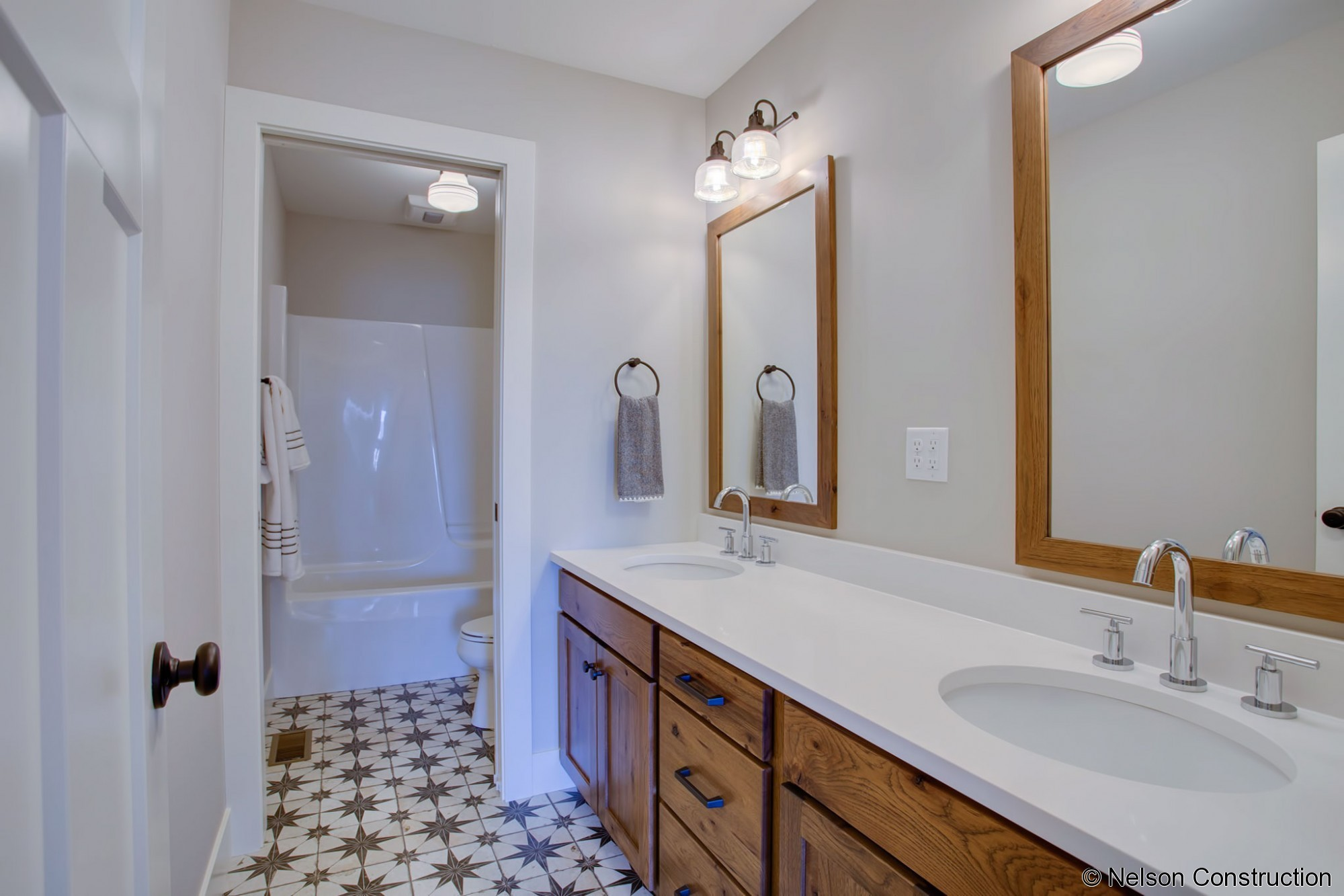 The guest bathroom of this Cherrydale plan is accented with vintage-inspired flooring and rustic hickory cabinets.