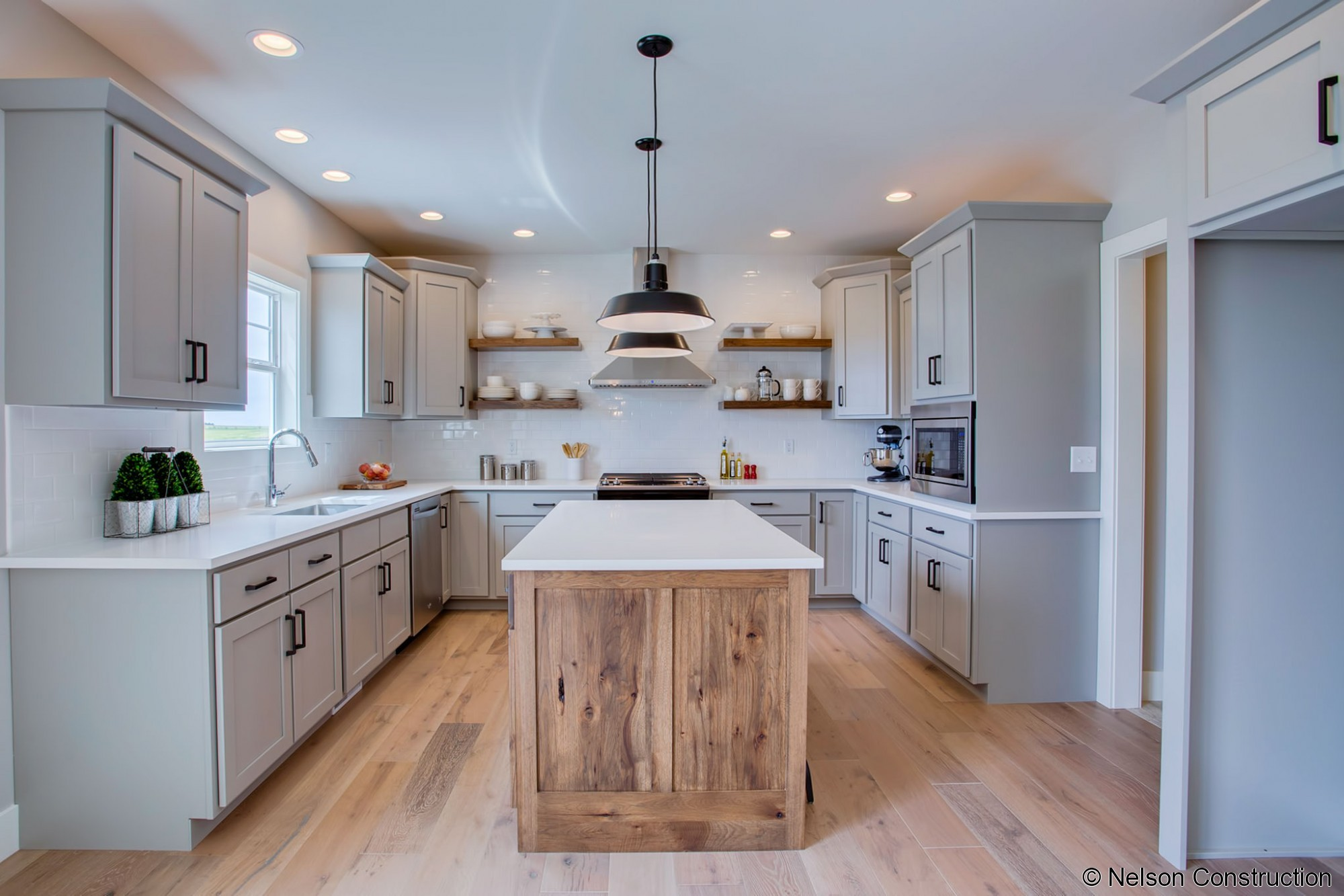 The kitchen of this new home by Nelson Builders is highlighted by the rustic hickory island and floating shelves.