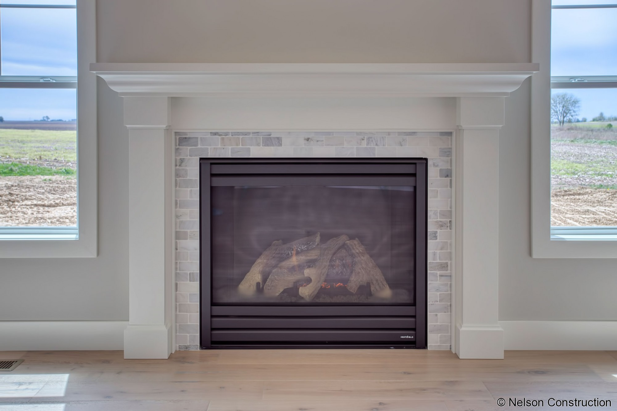 The fireplace of this Cherrydale plan home features a farmhouse-styled mantle surround with tumbled marble tile.