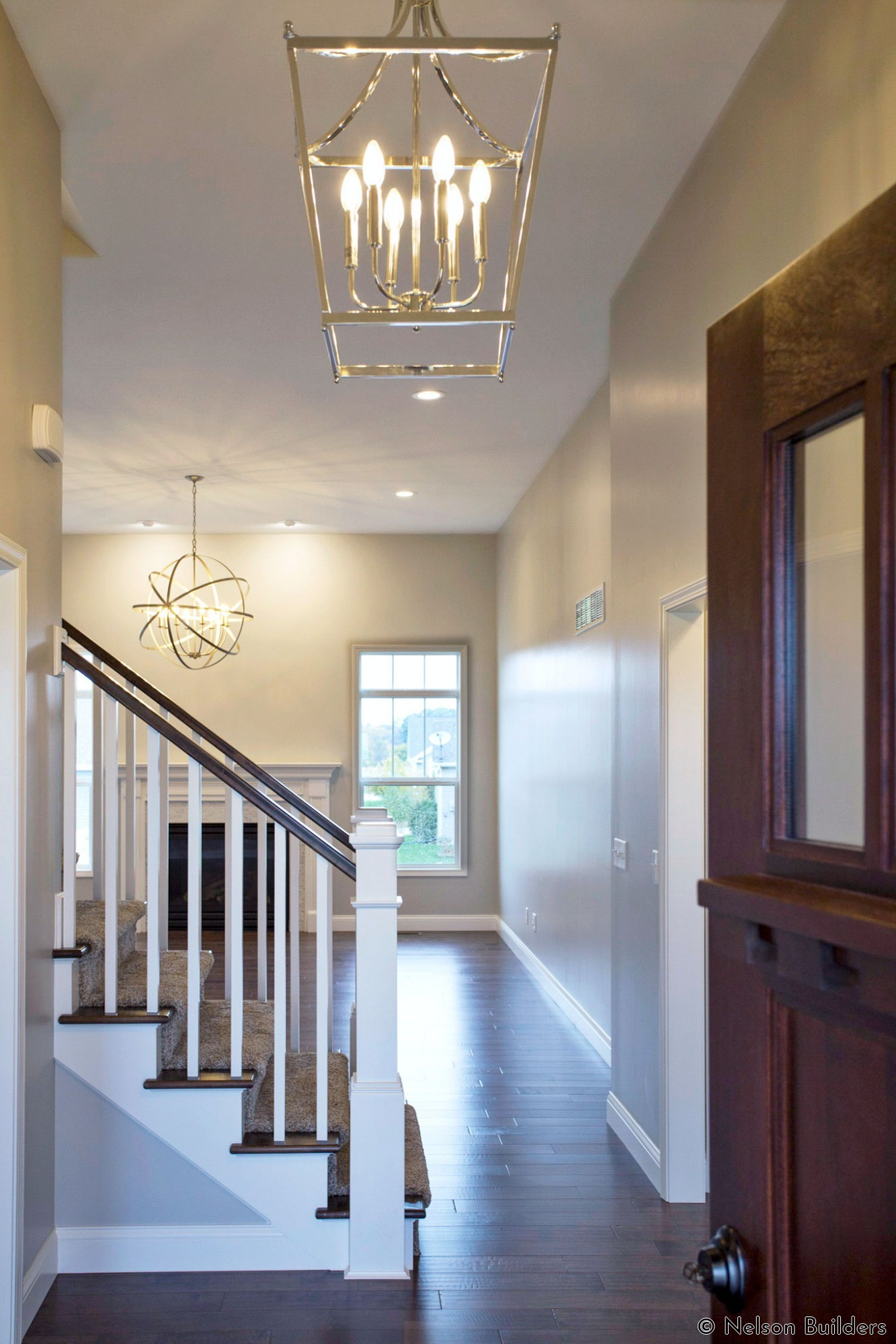 The wood front door opens into the grand foyer and great room of this new Cherrydale plan by Nelson Builders.