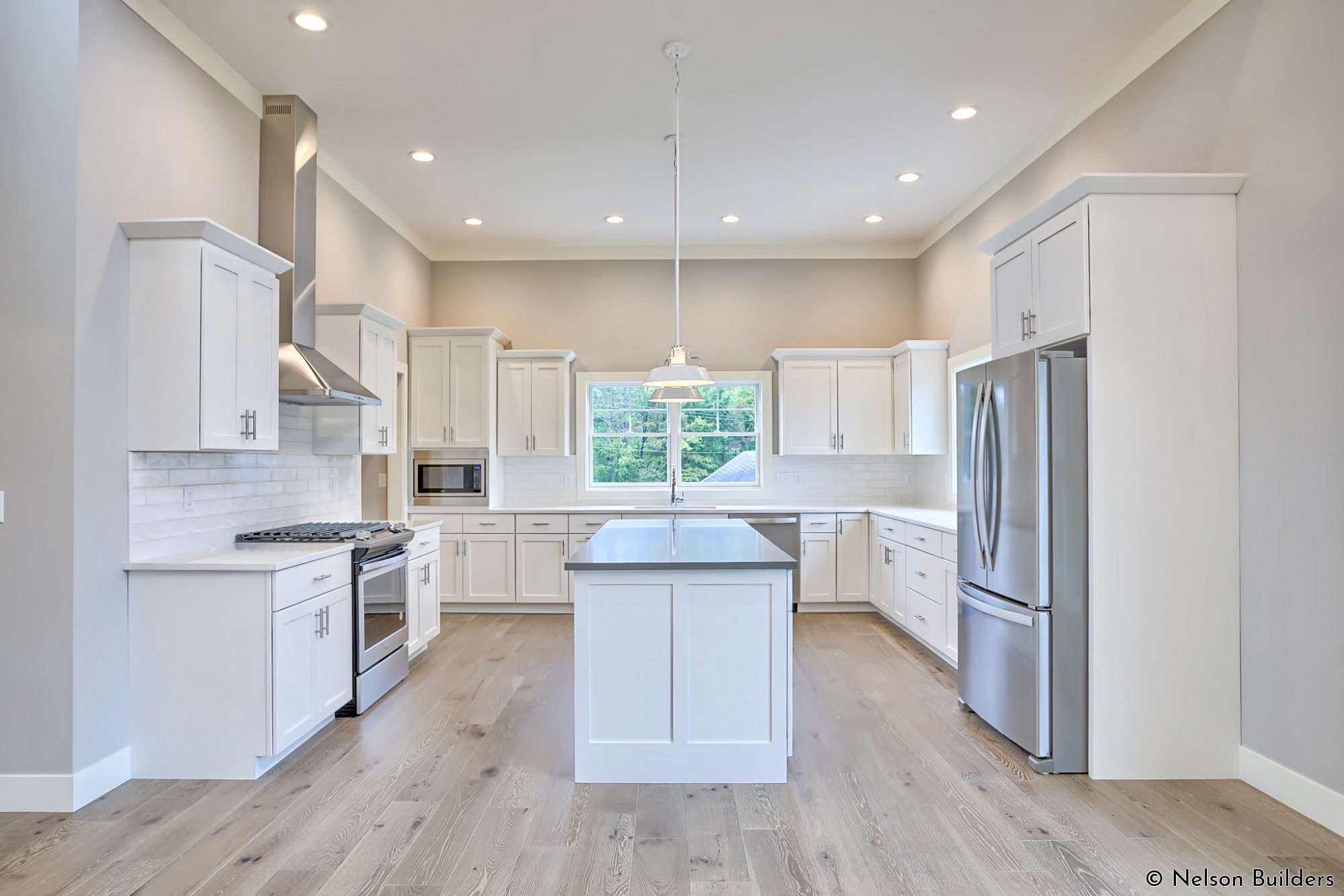 The large kitchen of this new custom plan features 11-foot ceilings and plenty of natural light.