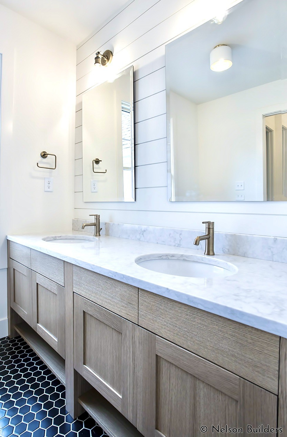 The kids bath features custom made white oak cabinets in front of a shiplap wall. Champagne bronze fixtures accent the clean color pallet.